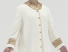 Cream polyester Roman style cassock with old gold piping, old gold cloth covered buttons, small Coronation Red/Gold/Purple brocade featured as a strip on a straight sleeve, shawl collar and as an insert in 3 of the 5 back pleats