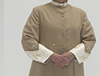 Tan Roman Style Cassock featuring old gold piping and cloth covered buttons and mini pleating from shoulder to waist